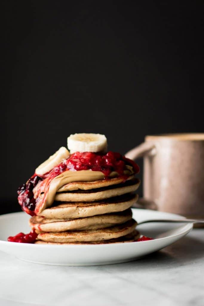 pancake stack with berries and banana slices