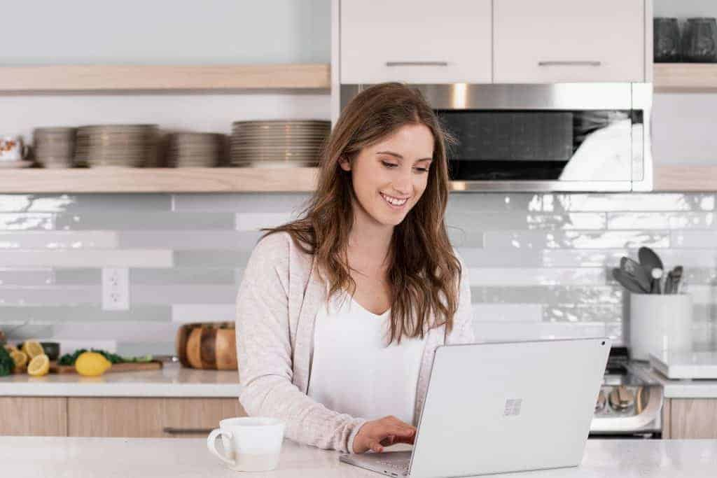 girl on a computer in white kitchen - media and brand services