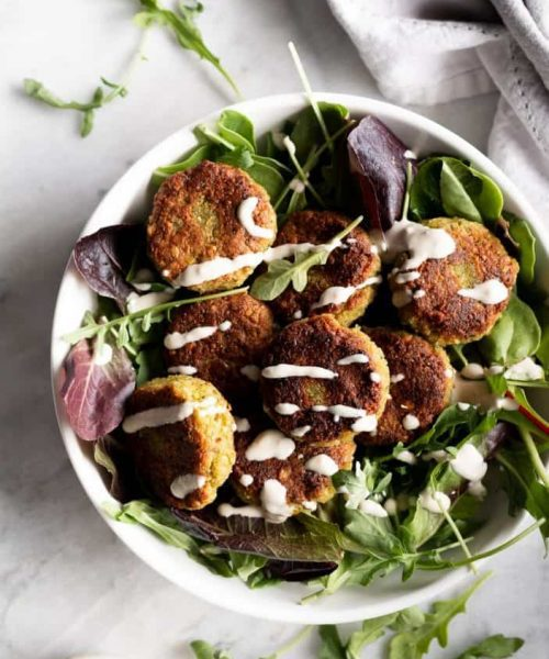 basic falafels in a bowl of greens