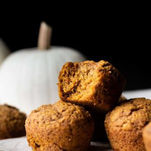 pile of pumpkin muffins from the side with bite taken