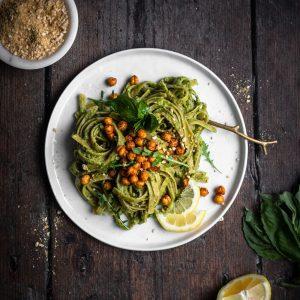 vegan avocado pesto pasta on a plate with chickpeas